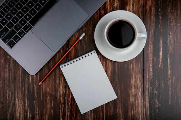 Tazza dello spazio della copia di vista superiore di tè con la matita e il taccuino del taccuino su fondo di legno