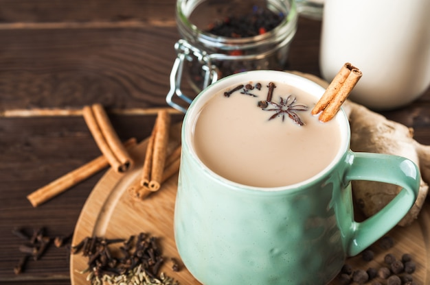 Tazza di argilla su una tavola di legno su uno sfondo scuro. una tazza di tè masala. spezie, chiodi di garofano, finocchio, cannella, cardamomo, latte.