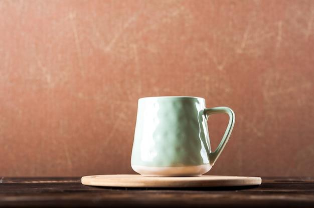 Tazza di argilla su una tavola di legno su uno sfondo scuro.