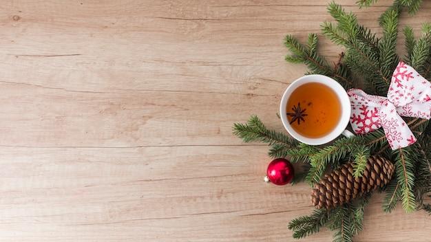 Tazza di bevanda vicino a conifere ramoscelli e strappi
