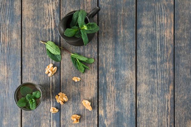 Tazza di bevanda vicino a lanciatore, ramoscelli di piante e noci sul tavolo