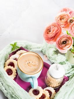Tazza di biscotti di caffè e fiori di ranuncolo rosa. colazione festiva madre giorno di san valentino
