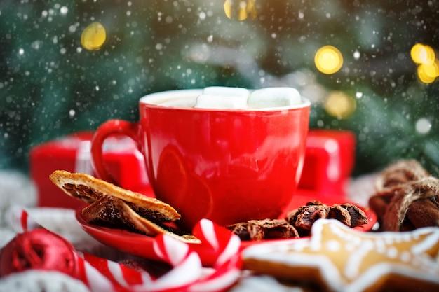Tazza di cacao, biscotti, regali e rami di abete su una tavola di legno bianca