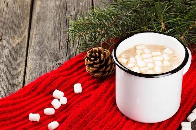 Tazza di cacao caldo con crema e caramelle gommosa e molle su oscurità