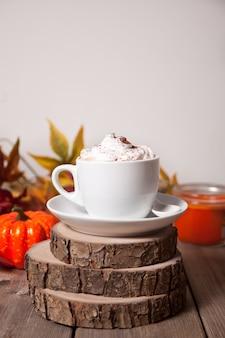 Tazza di cacao caldo cremoso con schiuma con foglie di autunno e zucche sullo sfondo