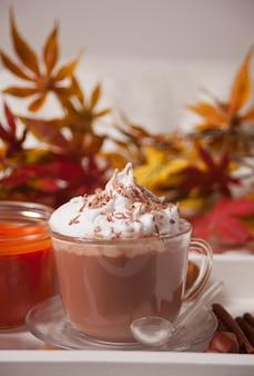 Tazza di cacao caldo cremoso con schiuma sul vassoio bianco con foglie di autunno e zucche sullo sfondo