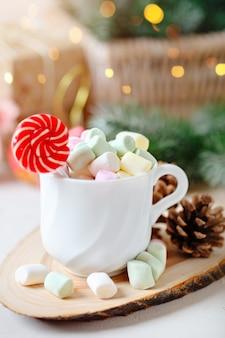 Tazza di cacao e caramelle gommosa e molle su uno sfondo chiaro