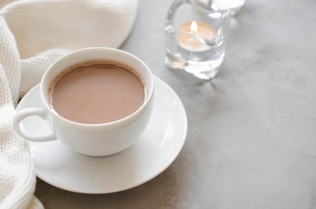 Tazza di cacao su un tavolo, candele e coperta a maglia.