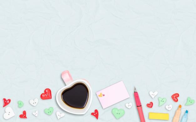 Tazza di caffè a forma di cuore con il simbolo dell'amore di colore su sfondo di carta riciclata di colore azzurro, design piatto laico, vista scrivania dall'alto.
