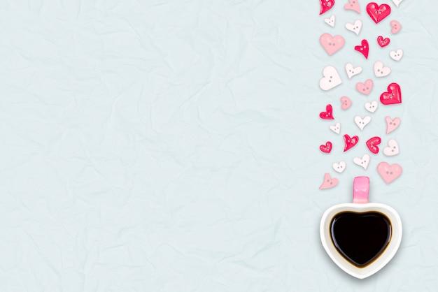 Tazza di caffè a forma di cuore con il simbolo di amore rosso su sfondo di carta riciclata di colore azzurro, design piatto laico, vista scrivania dall'alto. copia spazio a sinistra.