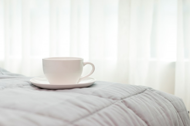 Tazza di caffè al mattino sullo sfondo del letto