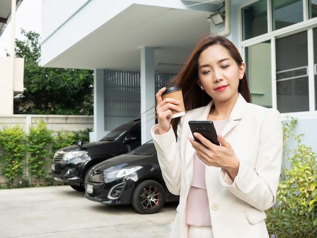 Tazza di caffè asiatica della tenuta della donna e smartphone usando mentre stando davanti alla casa.