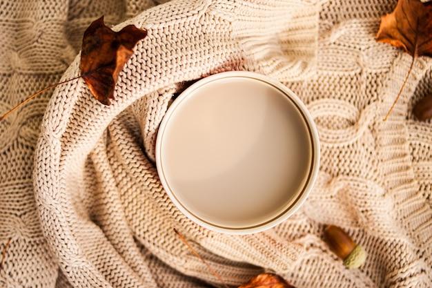 Tazza di caffè avvolta in un maglione di lana beige