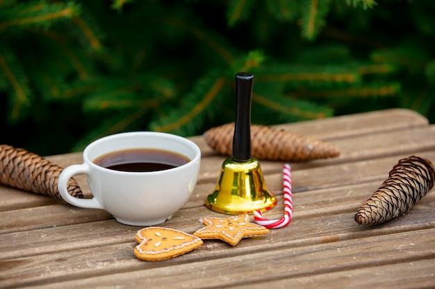 Tazza di caffè, bastoncino di zucchero e campana con i biscotti sulla tavola di legno con i rami attillati su fondo