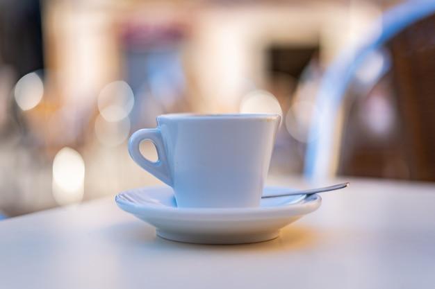 Tazza di caffè bianca in cima a un tavolo da bar