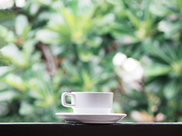 Tazza di caffè bianca sopra il fondo astratto floreale verde della sfuocatura.