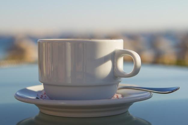 Tazza di caffè bianca sul tavolo in mare. concetto di vacanza estiva