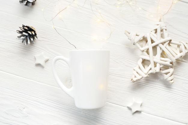 Tazza di caffè bianco con coni e stelle di natale.