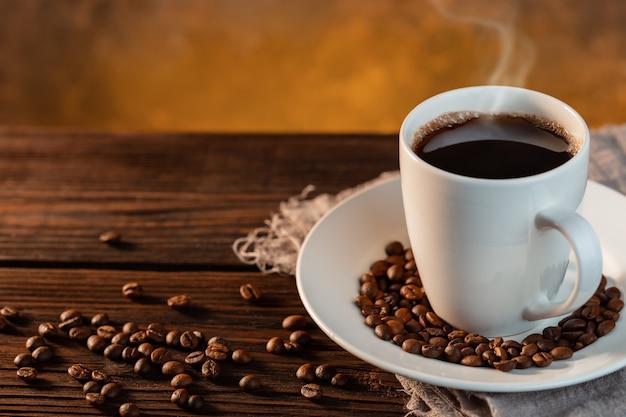 Tazza di caffè bianco e chicchi di caffè su fondo di legno