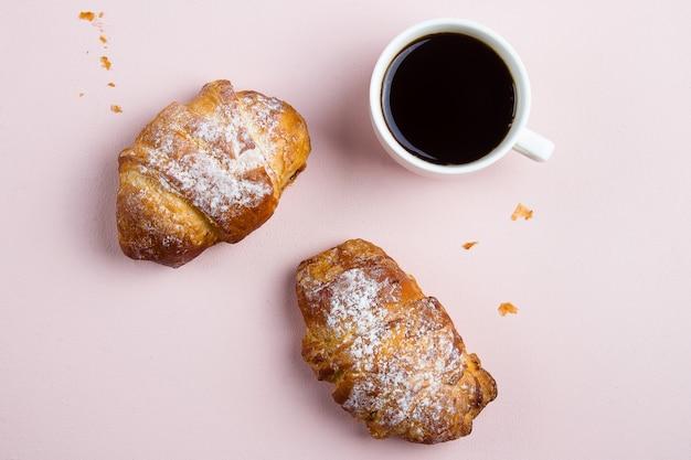 Tazza di caffè bianco e due croissant sullo sfondo rosa pastello. vista piana, vista dall'alto