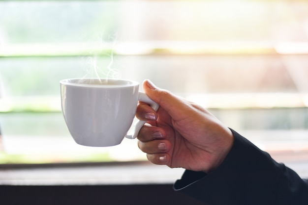 Tazza di caffè bianco in mano finestra della tazza di caffè della holding della donna di affari con luce solare di mattina