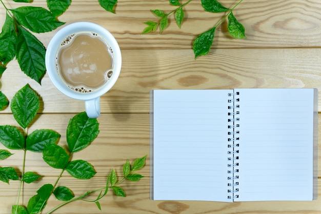 Tazza di caffè bianco, rami verde foglie e taccuino su un tavolo di legno.