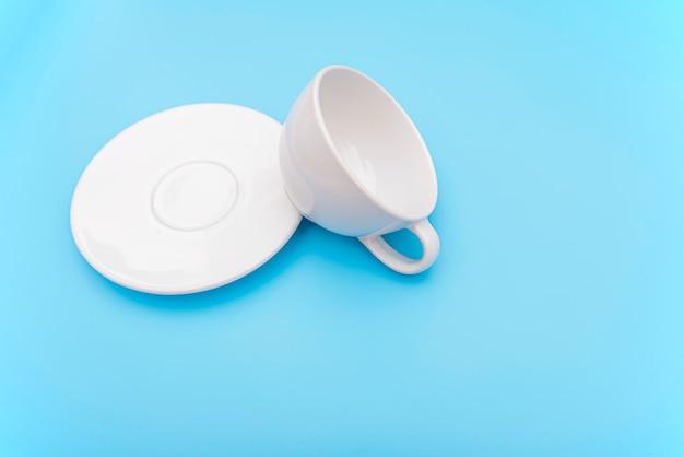 Tazza di caffè bianco vuota rovesciata o rovesciata, tazza con scodella