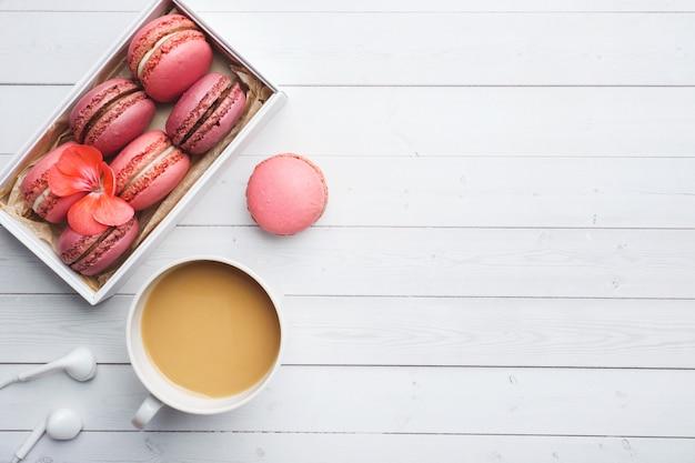 Tazza di caffè, biscotti del maccherone in una scatola, fiori su una tavola bianca. copia spazio. concetto bella colazione. disteso