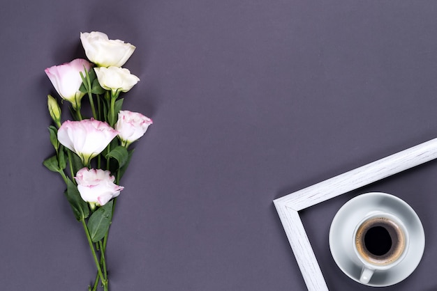 Tazza di caffè blu con l'eustoma rosa di fioritura del mazzo su un fondo di carta nero con copyspace, disposizione piana.