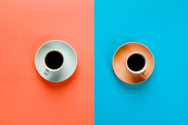 Tazza di caffè blu e marrone su un colorato arancione e blu.