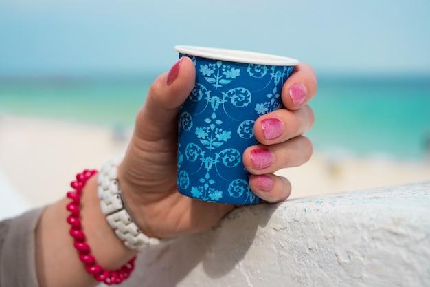 Tazza di caffè blu in una mano femminile