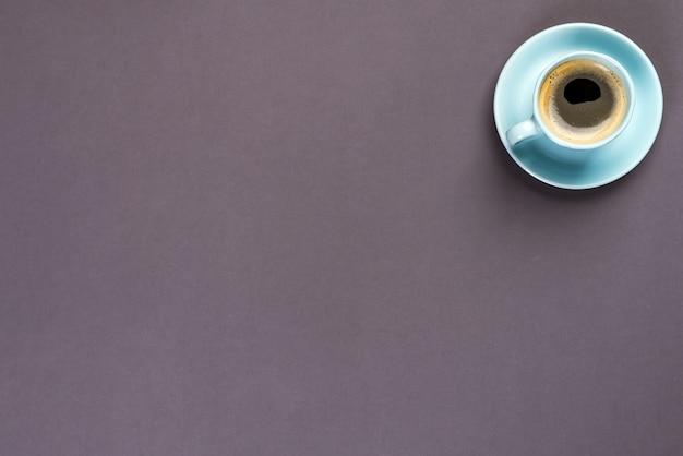 Tazza di caffè blu sopra i precedenti di carta neri con copyspace, disposizione piana
