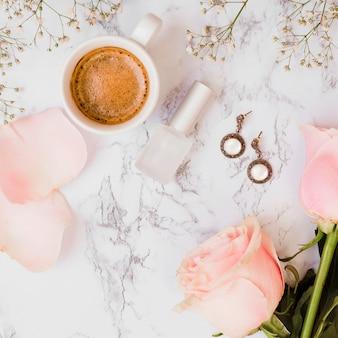 Tazza di caffè; bottiglia di smalto per unghie; rose; orecchini e fiori baby's-breath su sfondo con texture