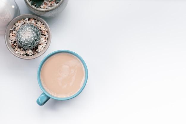 Tazza di caffè caldo con il cactus sugli oggetti della decorazione delle terraglie tazza da caffè calda sulla tavola bianca