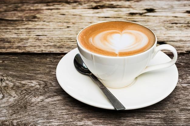 Tazza di caffè caldo d'annata con la bella decorazione di arte del latte sulla vecchia tavola di legno di struttura
