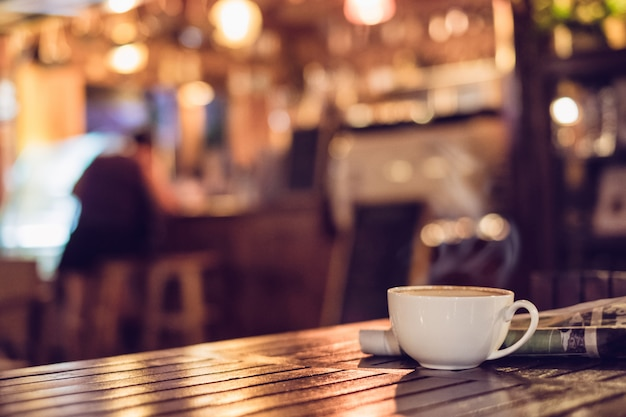 Tazza di caffè caldo del caffè espresso con il giornale sul fondo di legno della sfuocatura del bokeh di illuminazione della tavola
