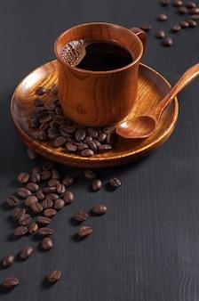 Tazza di caffè caldo e fagioli su un piatto di legno