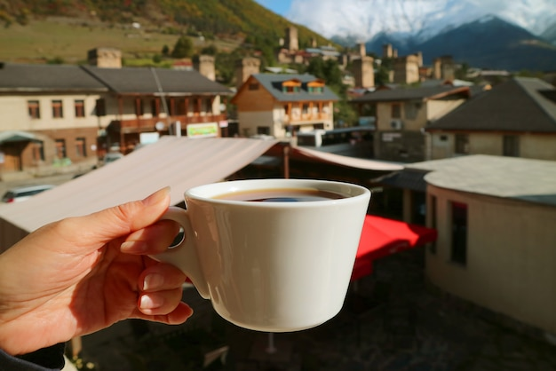 Tazza di caffè caldo in mano della donna contro sfocata bella città con montagne di neve