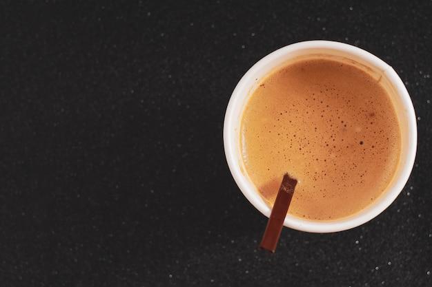 Tazza di caffè caldo in tazza di carta con schiuma di latte cremoso latte preso dalla vista superiore