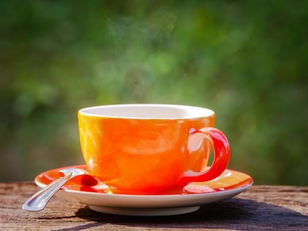 Tazza di caffè caldo su sfondo verde naturale al mattino