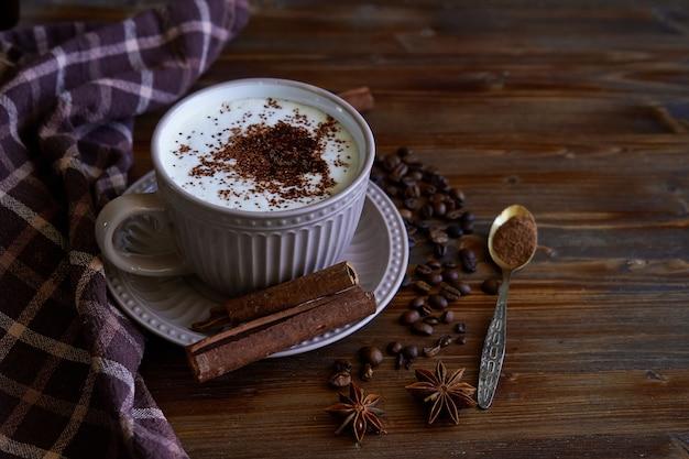 Tazza di caffè capuccino con cannella e chicchi di caffè su copyspace in legno