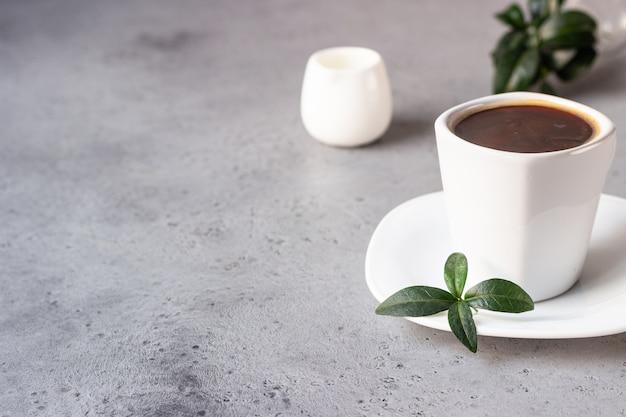 Tazza di caffè, chicchi di caffè e brocca di latte su sfondo grigio pietra copia spazio per il testo