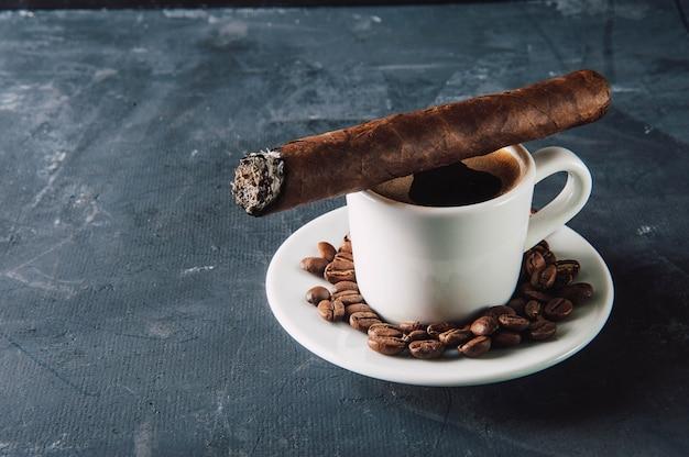 Tazza di caffè, chicchi di caffè, posacenere con sigaro su oscurità