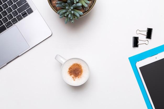 Tazza di caffè circondata dai dispositivi dell'ufficio su fondo bianco