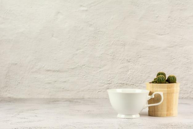 Tazza di caffè classica bianca sullo scrittorio bianco nella stanza della cucina.