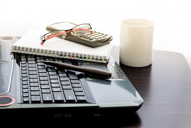 Tazza di caffè, computer portatile, penna, calcolatrice, blocco note e bicchieri sul tavolo di legno