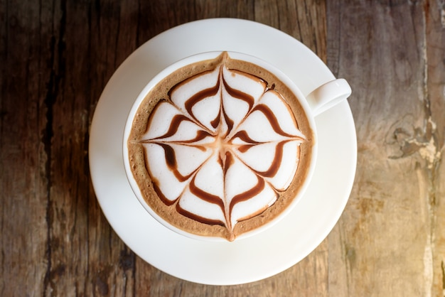Tazza di caffè con bella arte di latte sul fondo della tavola in legno