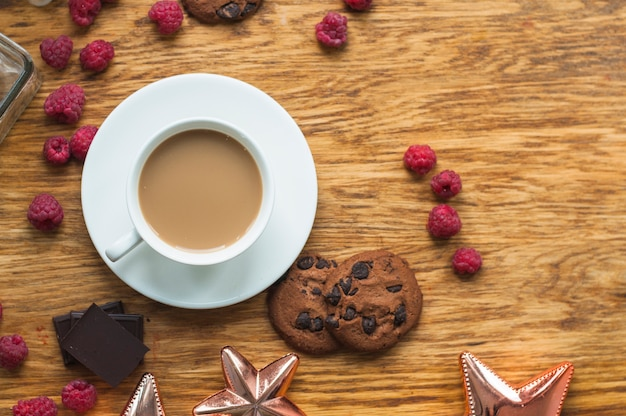 Tazza di caffè con biscotti; lamponi e pezzi di barretta di cioccolato sul tavolo di legno