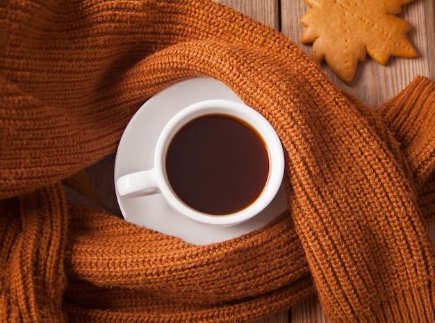 Tazza di caffè con biscotto e maglione marrone sul tavolo di legno