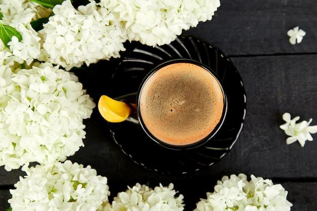Tazza di caffè con bouquet di ortensie